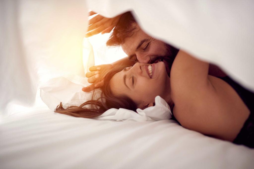 Un couple au lit qui sourit et s'embrasse