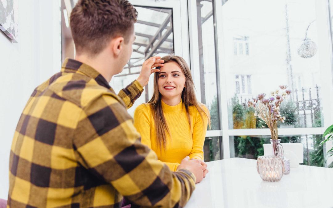 Un homme qui touche le visage d'une femme souriante