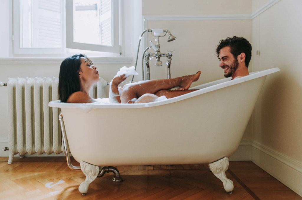 Un couple qui prend un bain dans une baignoire et qui joue avec la mousse.