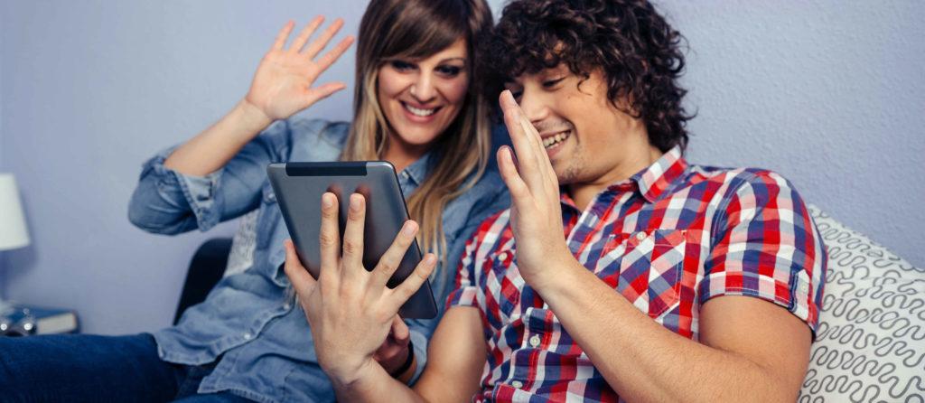 Un couple qui salue en souriant un proche à travers un écran de tablette.