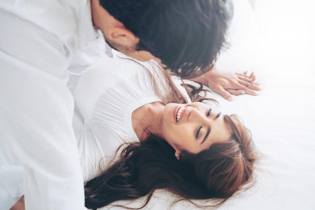 Un couple sur un lit qui est heureux. Ils vont faire l'amour.