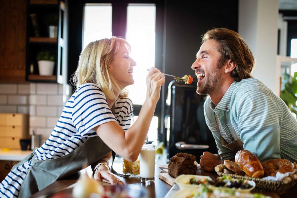 Une femme qui donne à manger à un homme dans leur maison
