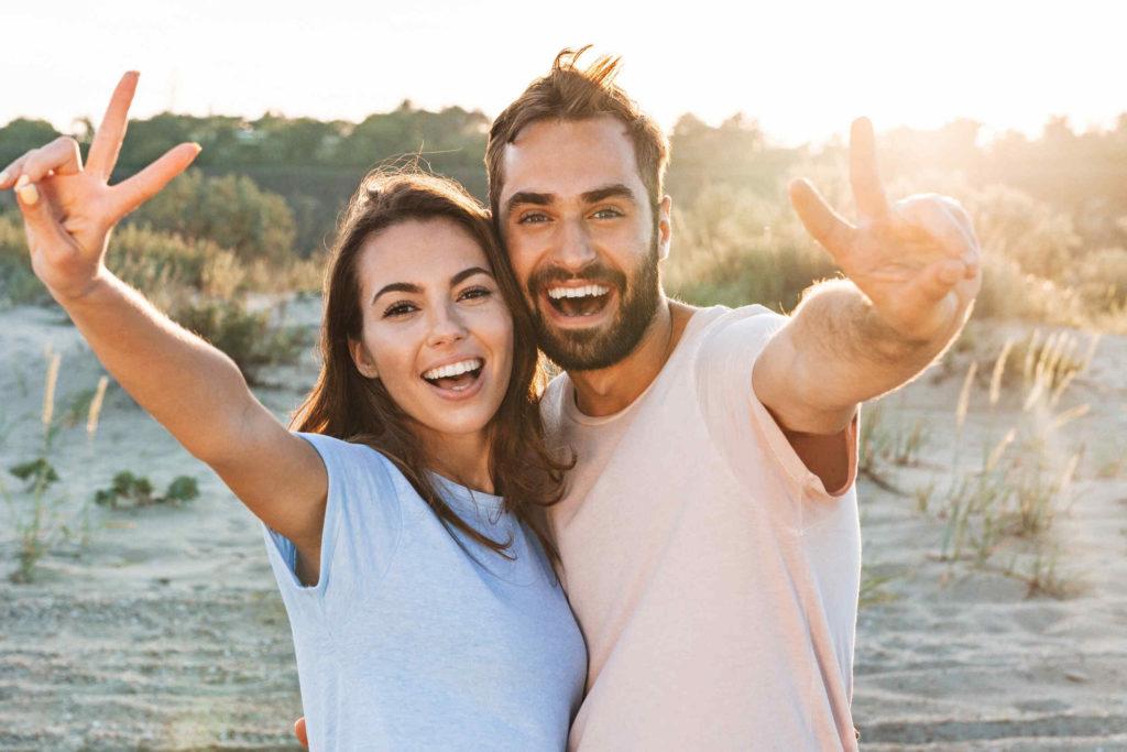 Un couple qui s'amuse à la plage. Ils sont heureux et souriants. Cet état d'esprit va faire durer leur couple.