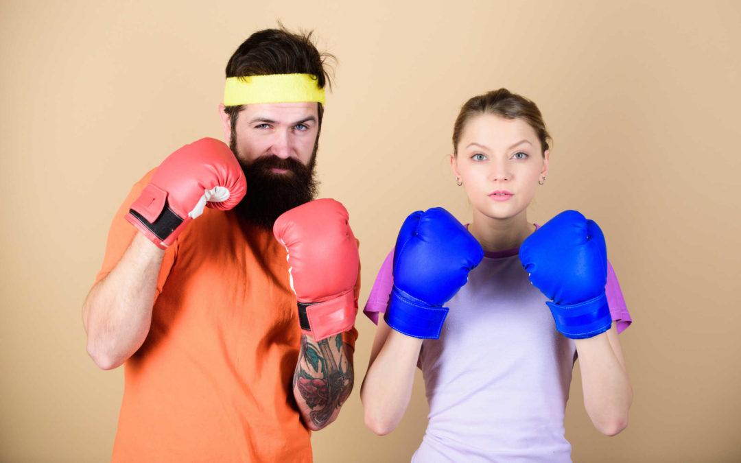 Une femme et un homme qui portent des gants de boxe. Ils vont peut-être se battre pour gagner du respect l'un de l'autre.