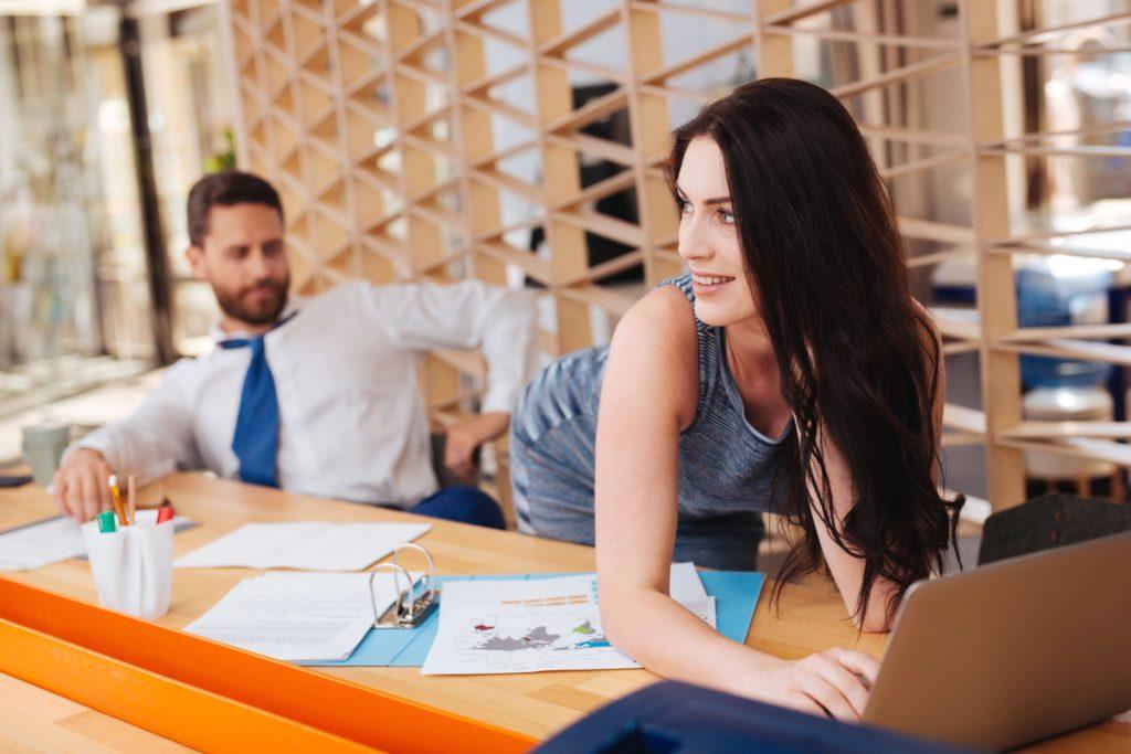 Une femme dans un bureau se penche pour exciter un homme qui la regarde.
