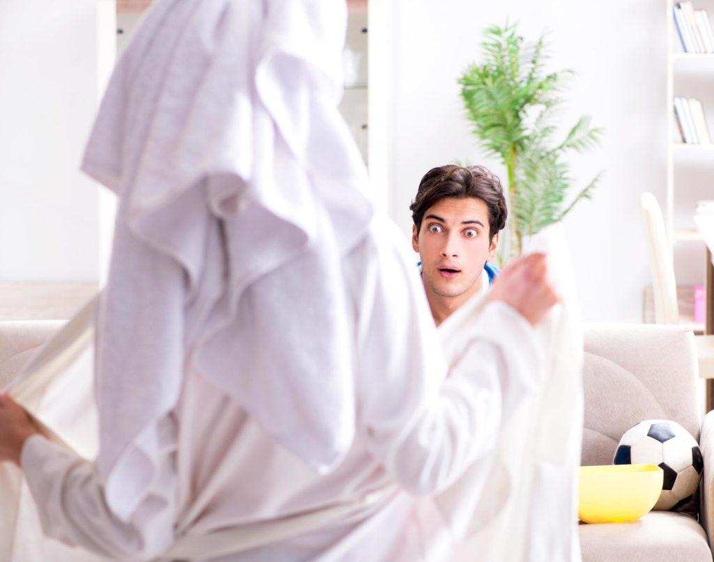 Une femme ouvre son peignoir pour se montrer nue face à son homme. Il est surpris.