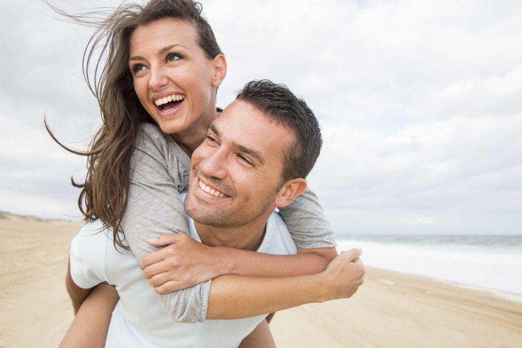 Un homme et une femme sur une plage. Ils sont heureux et s'amusent.