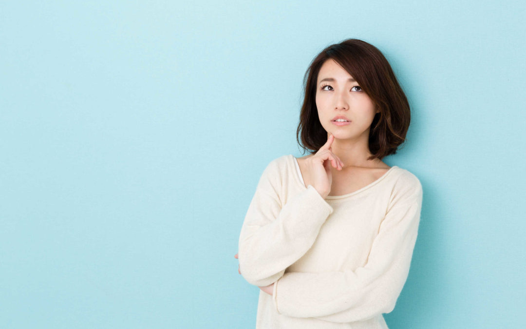 Une femme qui doute avec son doigt sur la bouche. Elle regarde en l'air. Elle ne veut pas s'engager avec un homme ?