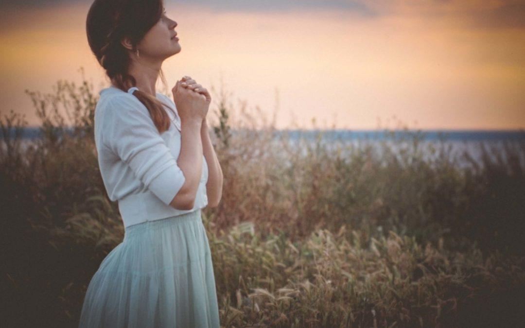 Une femme en robe blanche qui prie vers le ciel. Être une femme vierge doit la questionner.