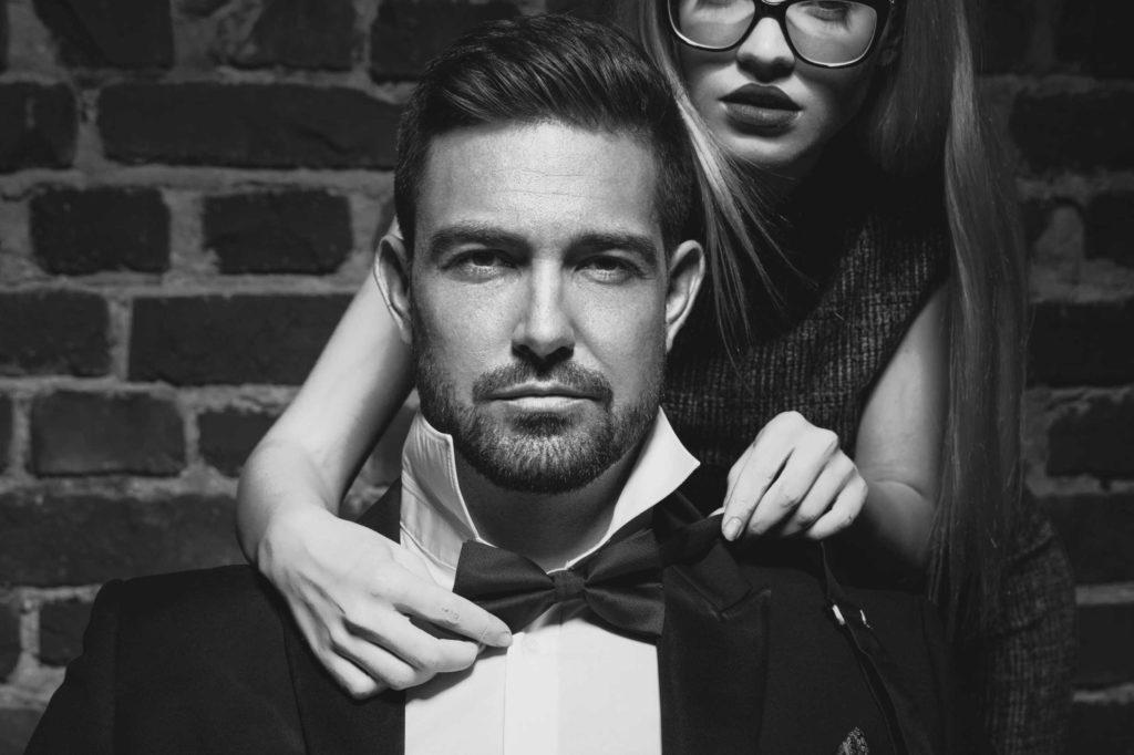 Un homme en costard qui semble sûr de lui. Une femme derrière lui remet son nœud papillon. La sexualisation est à son comble.