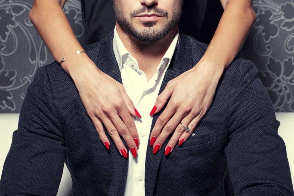 Un homme en costard qui se fait toucher par une femme. Il a l'air attirant.