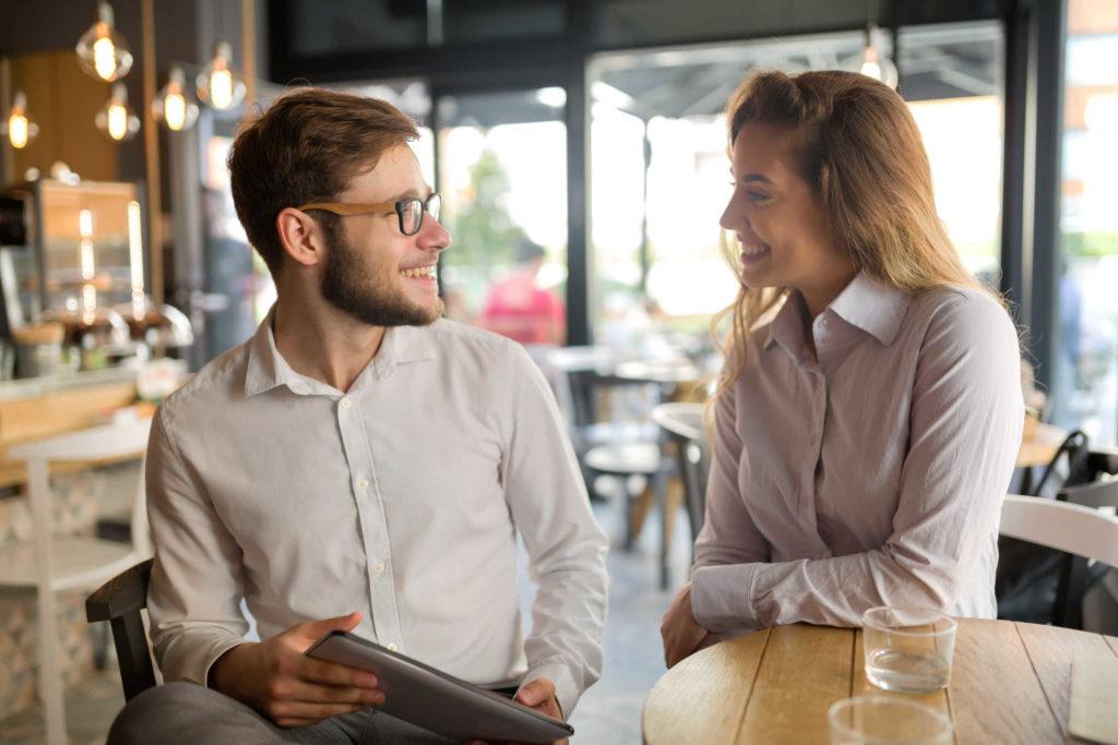 Un homme et une femme dans un café. Ils se sourient mutuellement.