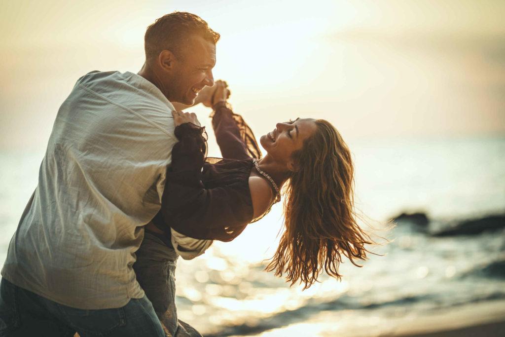 Un couple qui s'amuse sur la plage en dansant.
