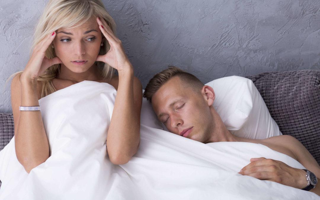 Une femme est dans un lit avec un homme qui dort. Elle semble inquiète des erreurs sexuelles qu'a commises l'homme.