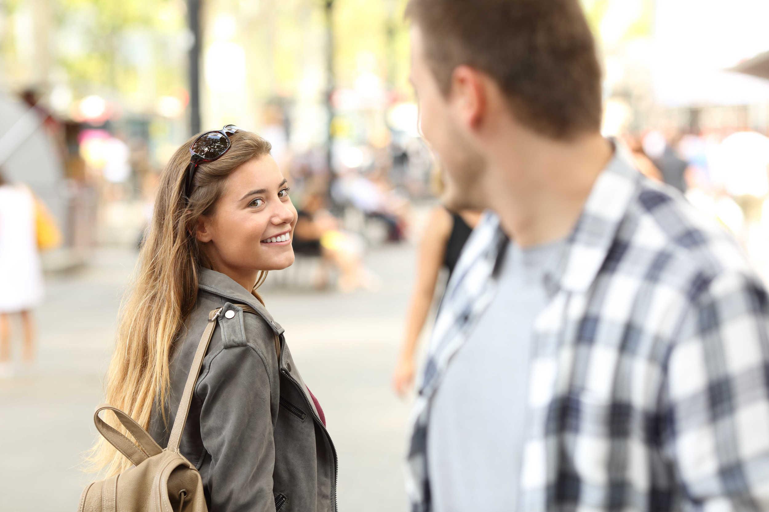 Une femme dans la rue regarde un homme. Elle semble l'attirer.