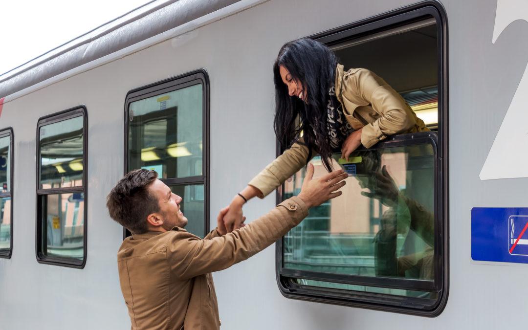 Un homme et une femme se retrouvent dans une gare. Ils veulent s'embrasser à travers la vitre du train. Ils sourient.
