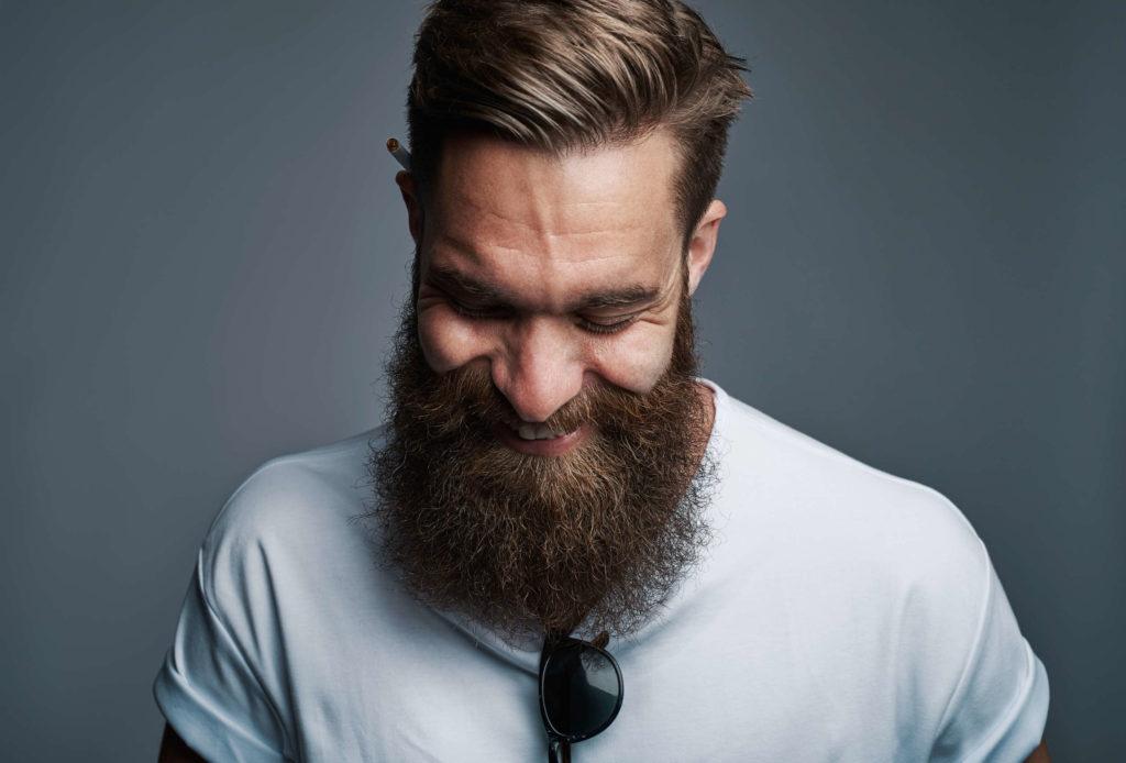 Un homme à barbe longue sourit. Il semble gêné ou timide.