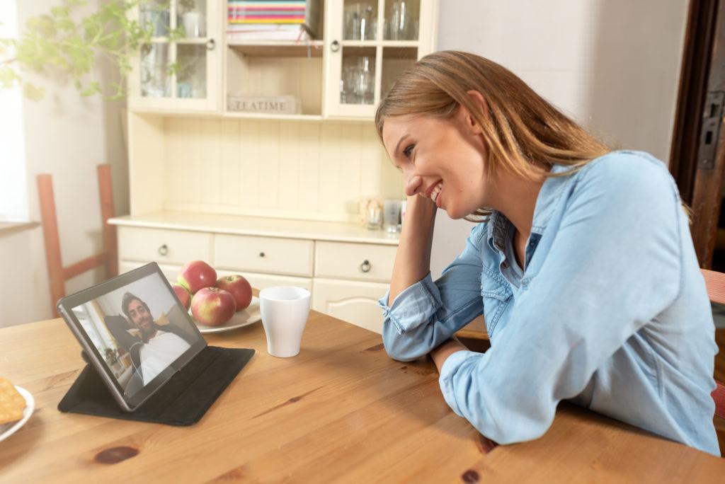 Une femme dans sa cuisine est devant son ordinateur. Elle parle à un homme sur son ordinateur en vidéo. Elle sourit. Voilà une bonne façon de savoir comment réussir une relation à distance.