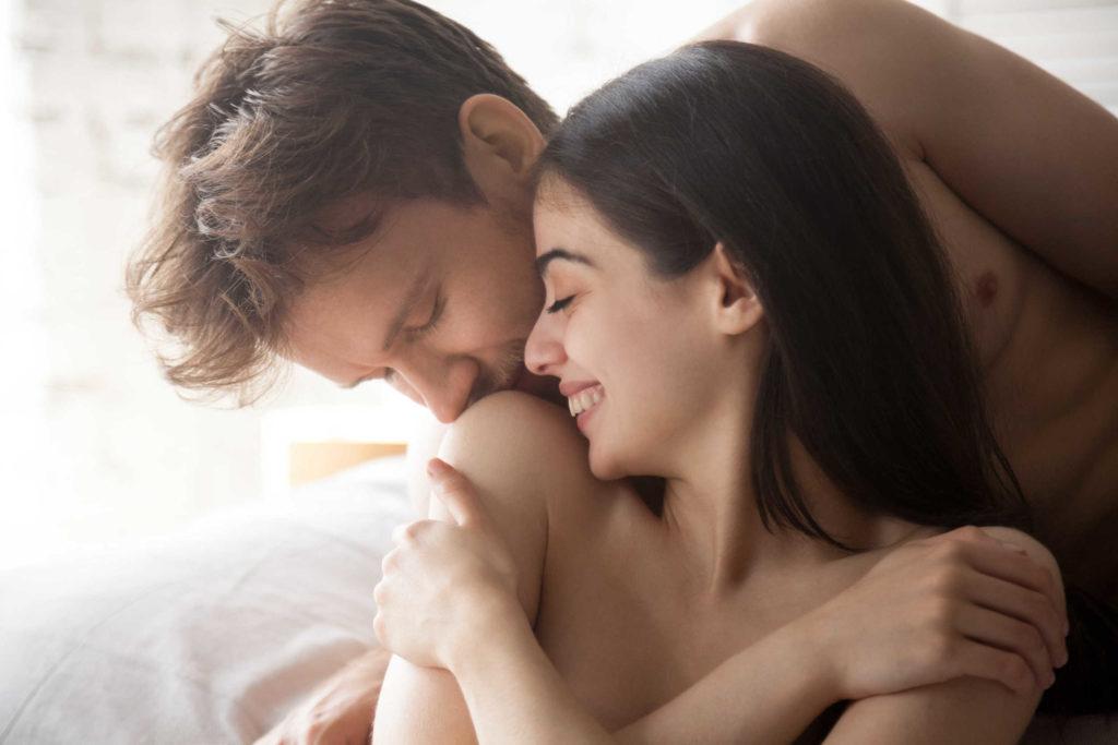 Un homme et une femme nus dans un lit. L'homme embrasse l'épaule de sa partenaire qui sourit.