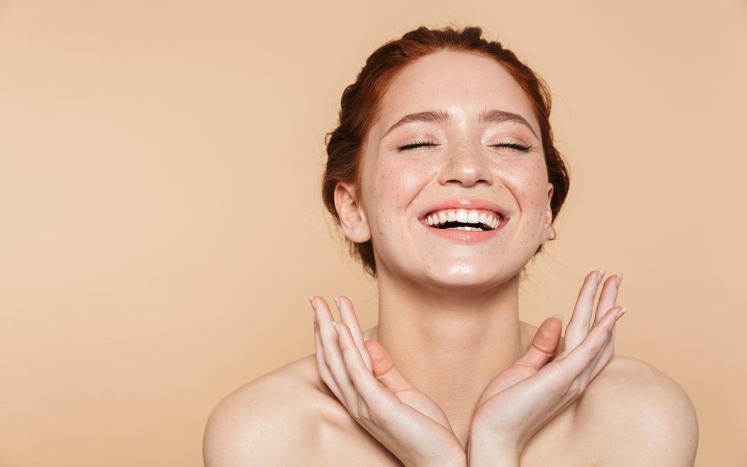 Une femme rousse sourit. Elle semble nue. Elle accepte son corps.