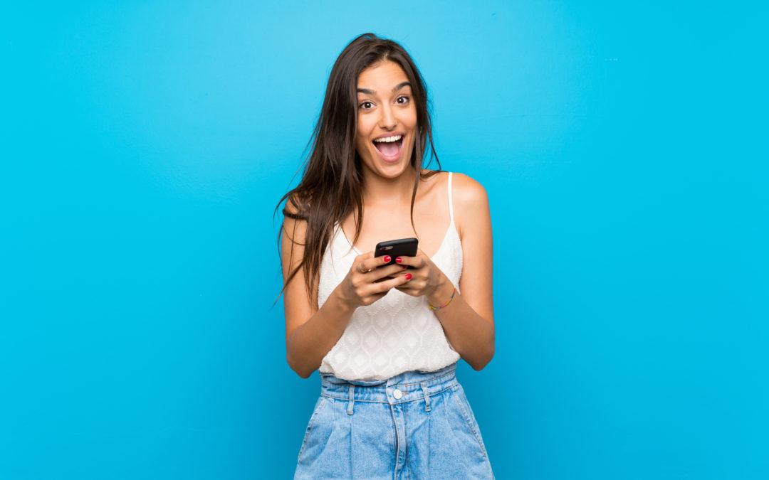 Une femme avec son téléphone qui sourit. Elle a reçu un message d'un homme qui lui manque.