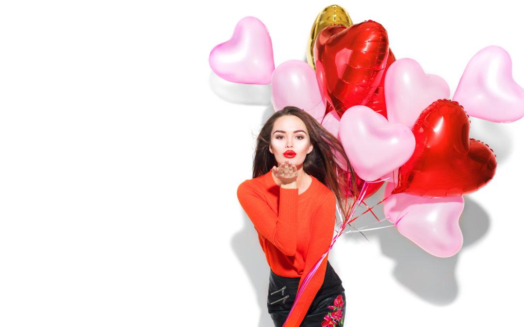 Une femme qui porte des ballons en forme de cœur. Elle fait un bisou.