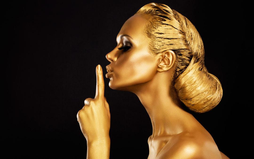 Une femme teintée d'une couleur dorée qui met un doigt devant sa bouche. Elle ne veut pas dire certaines choses sur la sexualité.