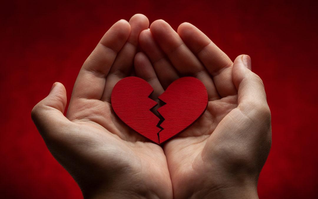 Deux mains tiennent en leur creux un cœur fissuré. Cette personne doit se demander comment surmonter une rupture.