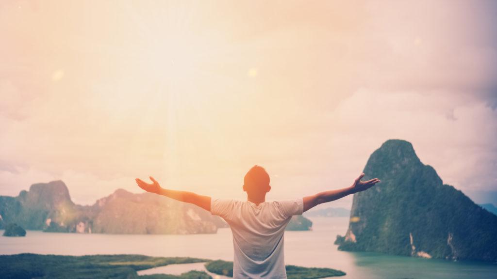 Un homme en hauteur regardant les montagnes et la mer. Il lèves les bras vers le ciel. Il est épanoui après sa rupture sentimentale.