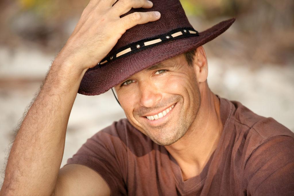 Un homme avec un chapeau sourit. Il a un regard attirant.