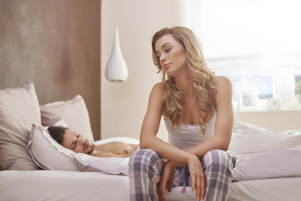 Une femme boude sur son lit. Son homme dort à côté. Il n'a pas l'air d'être un bon coup. Elle déteste d'être seule après le sexe.