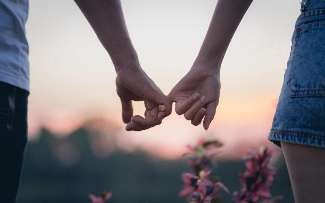 Une femme et un homme se tiennent la main par le petit doigt, c'est très romantique. On peut y voir différents types d'amour.