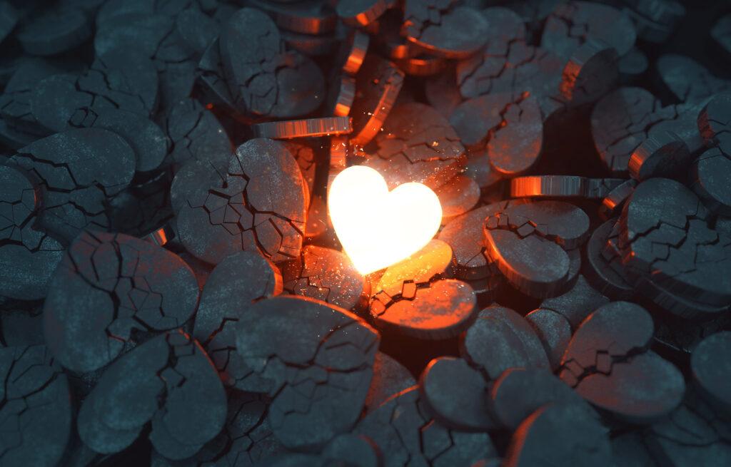 Un cœur rougeoyant au milieu de cœurs en charbon. Cela symbolise la rupture amoureuse.