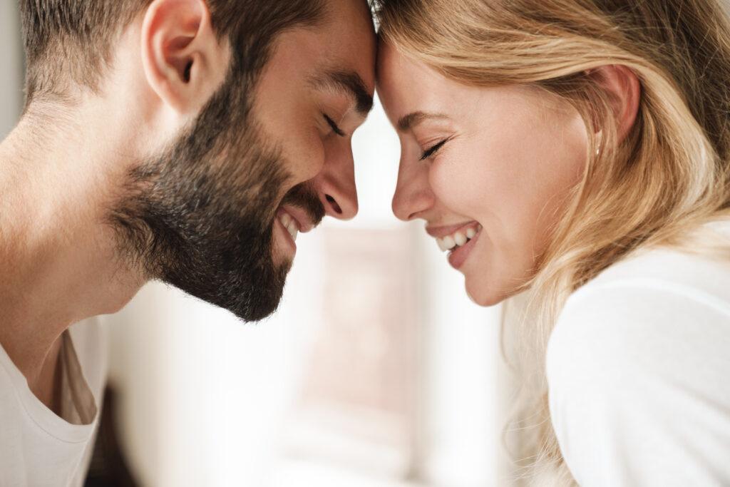 Un homme et une femme qui se touchent le front en souriant. Ils tombent amoureux.