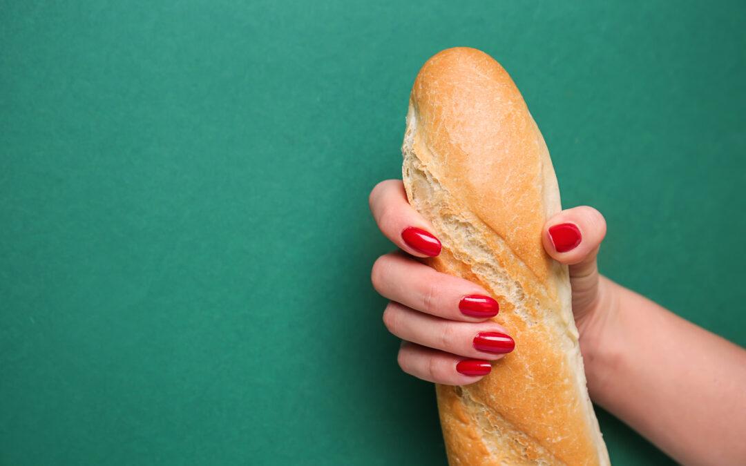 La main d'une femme tient une grosse baguette. C'est une métaphore pour désigner comment avoir un plus gros pénis.