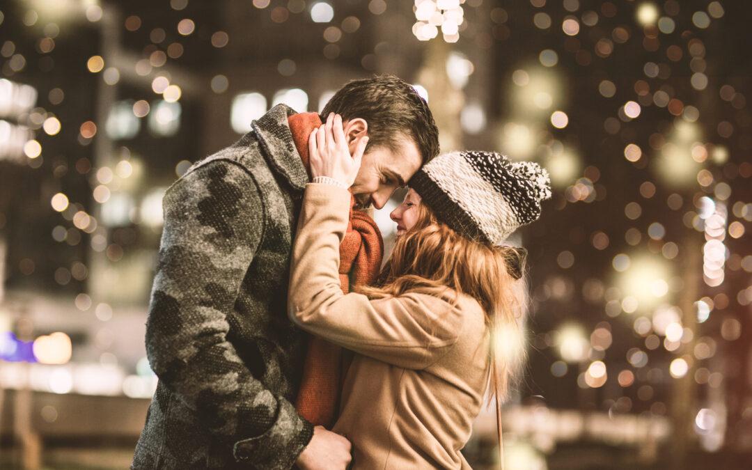 Un couple romantique en hiver au milieu des lumières. Il est heureux.