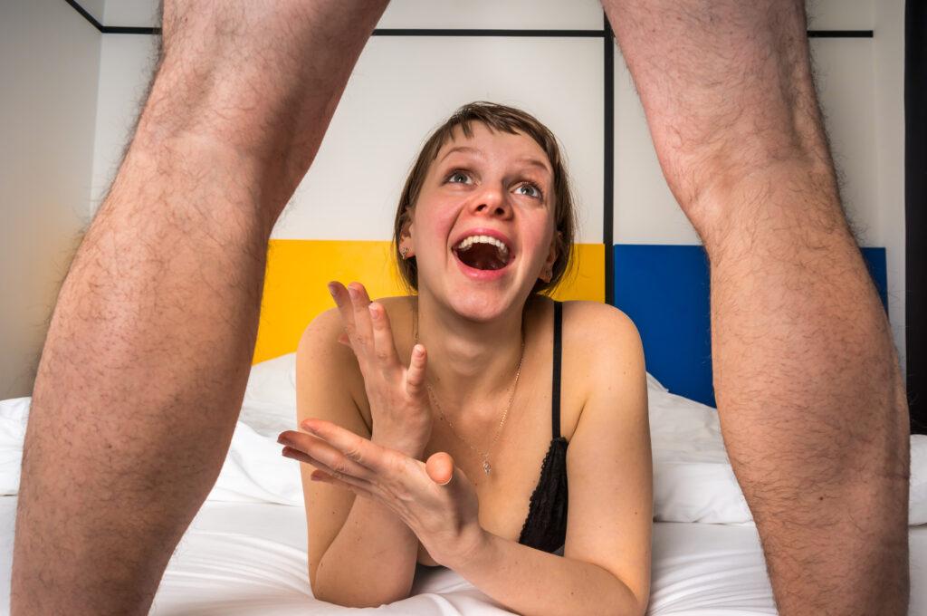 Une femme regarde sous les jambes d'un homme. Il semble être fier de la taille de son pénis.