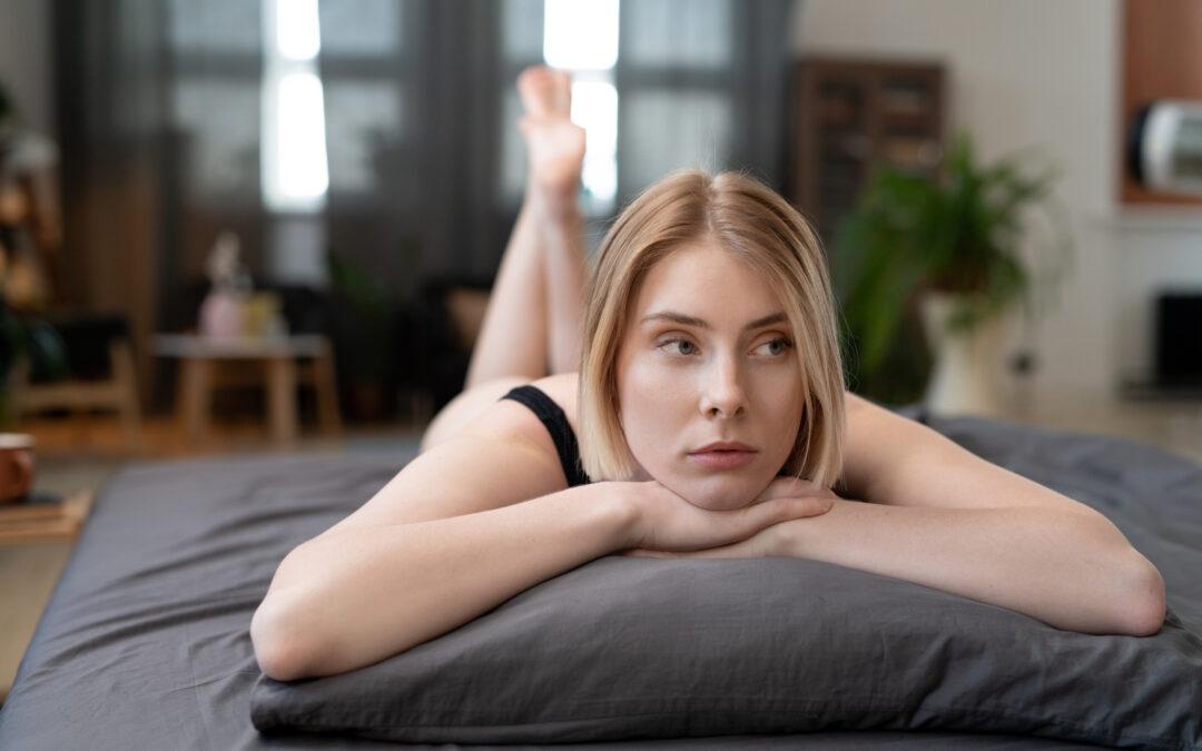 Une femme blonde allongée sur le lit. Elle semble pensive. Peut-être est-elle victime de l'anorgasmie ?