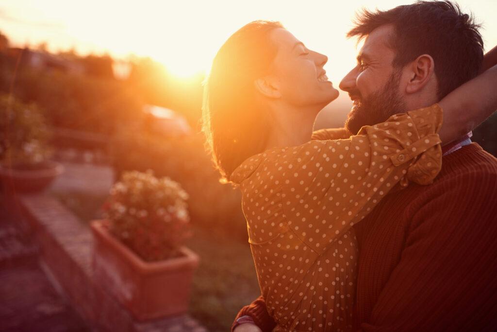 Un homme et une femme s'enlacent sous un coucher de soleil. C'est une belle relation.