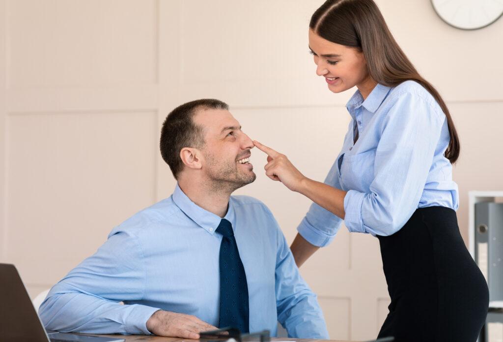Une femme qui taquine un homme au bureau. Elle pose son doigt sur son nez. Voilà de quoi plaire à un homme.