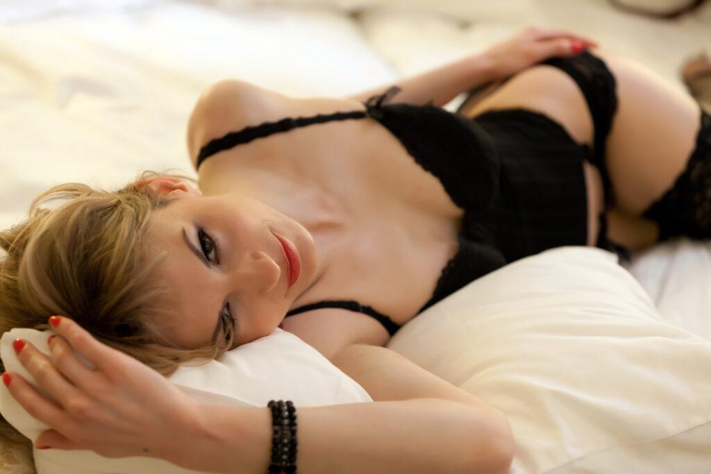 Une femme blonde en lingerie noire allongée sur le lit. Elle sourit.