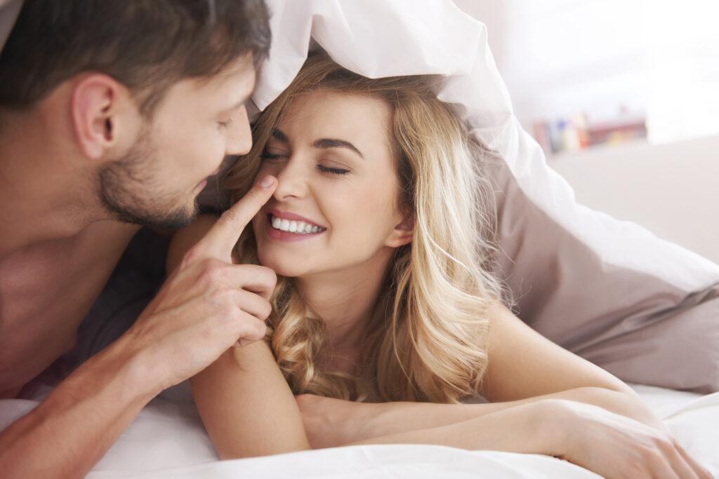 Un homme et une femme dans un lit. Ils s'amusent. L'homme fait ce qu'il faut pour séduire une femme.