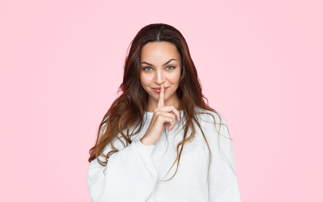 Une femme qui met un doigt devant sa bouche. Elle cache un secret sur ce que les femmes ne diront jamais aux hommes.