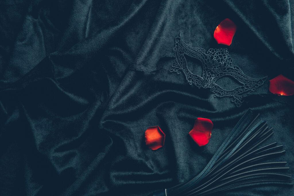 Un masque noir fantaisiste sur un drap soyeux avec es pétales de rose rouge. Cela évoque l'échangisme et le fétichisme.