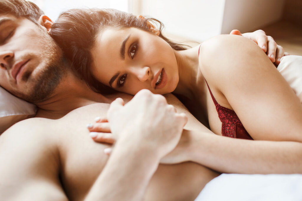 Une femme dans les bras d'un homme au lit. Cette image reflète ce qui attire les femmes.