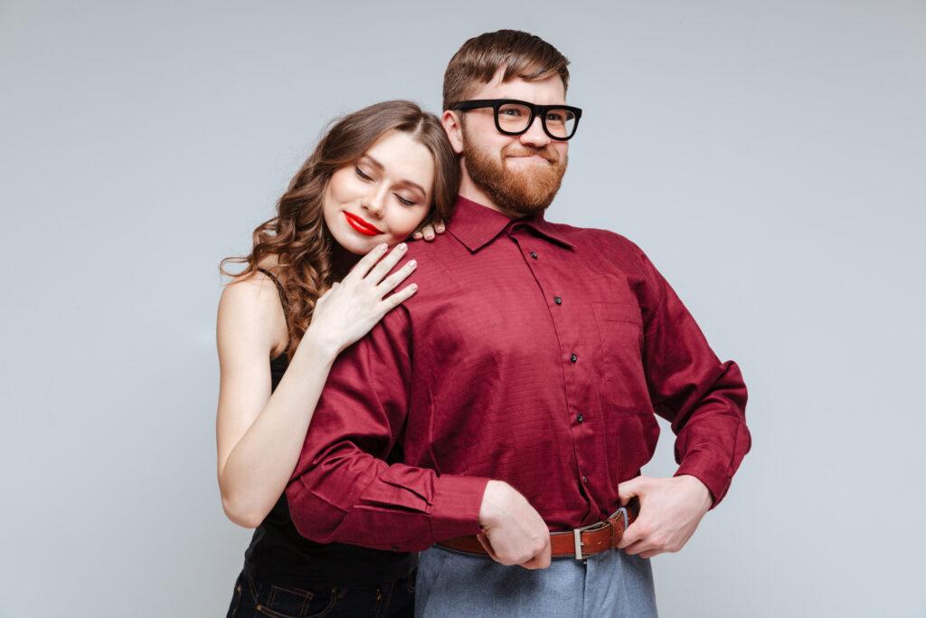 Un homme timide et une femme qui l'enlace. L'homme est fier et semble savoir comment plaire à une femme.