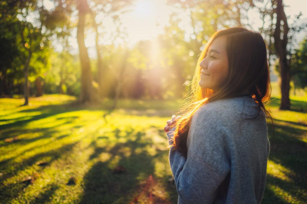 Une femme au soleil qui a l'air heureuse. C'est important de s'aimer soi-même !